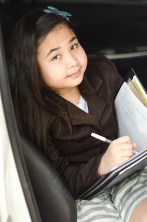 little business girl writing something on folder in her car