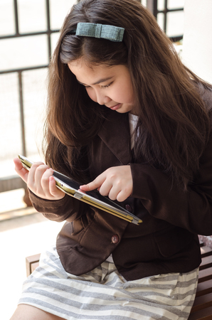 Young business girl using tablet computer and sitting on wooden chair. Stock Photo