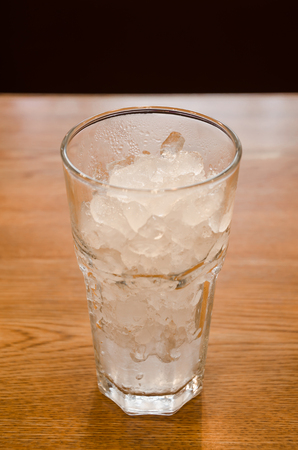 crushed ice in glass on wooden table.