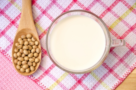 Soybean on wooden spoon and soy milk in a glass, on wooden table  Stock Photo