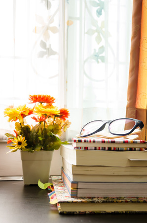 books and the glasses on table, near windows