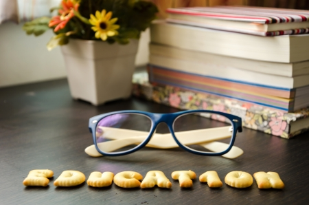 The words: education made of cookies, glasses and books on black table.