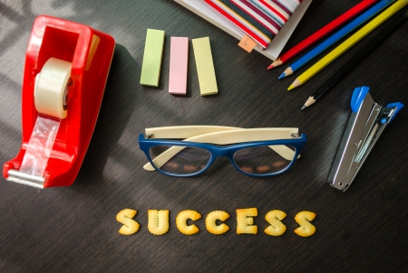The words: success made of cookies, glasses and stationeries on black table. Stock Photo