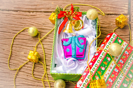Christmas gift box with golden small bell over wooden table. Stock Photo