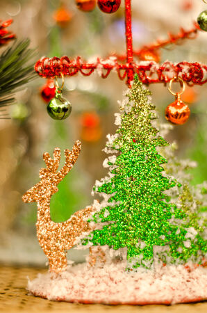 Christmas tree and gold reindeer decoration with bokeh background.