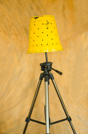 yellow floor lamp, D.I.Y by pot and tripods, isolated over vintage wall.