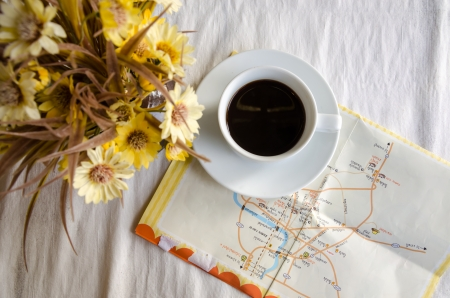 cup of coffee, flower pot and map on table. Stock Photo