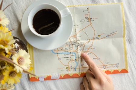 Close up of a hand pointing location on a map, White Coffee Mug. Stock Photo