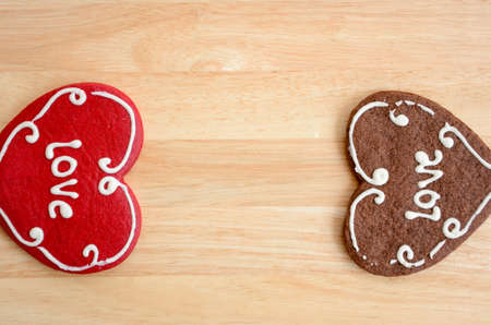 Valentine cookies with the words love on wooden table, red and brown