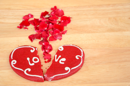 Cracked heart shaped cookie decorated with red icing photo