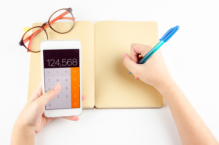 hand using mobile phone with calculator app and writing on a blank book. isolated white background. Stock Photo