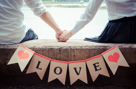 Young couple in love holding hands and love label.