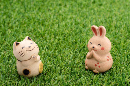 rabit: Decorative item - Japanese lucky cat and happy rabbit praying on the grass Stock Photo