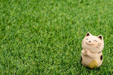 decorative item: Decorative item - Japanese lucky cat praying on the grass