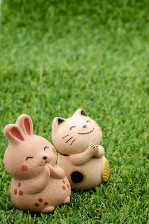 decorative item: Decorative item - Japanese lucky cat and happy rabbit praying on the grass Stock Photo