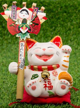 elemento decorativo - gatto fortunato giapponese sull'erba