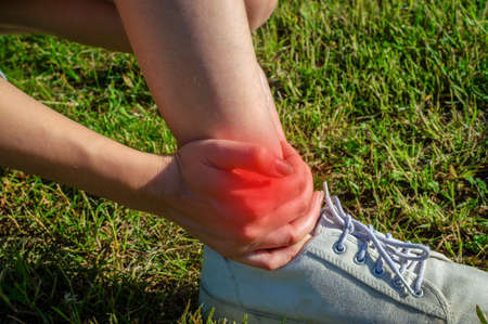 Young woman touching painful twisted ankle, female sport running ankle sprain, legs have problem, accident, hand massaging her leg pain after exercise in outdoor park