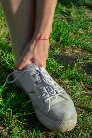 Runner girl outdoors on grass touching painful twisted ankle. Leg injury concept. Vertically.