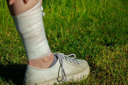sport runner woman cramps in leg and feel pain. girl bandages her knee ankle painful injury outside after exercise workout in nature road. Sports injuries concept