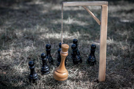 Black chess pawns have killed the king. The chess king is hung on the gallows after defeat. The concept of losing a war, uprising, revolution, loss of power, dethroning.