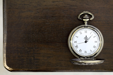 hands in pockets: Antique pocket watch on a table