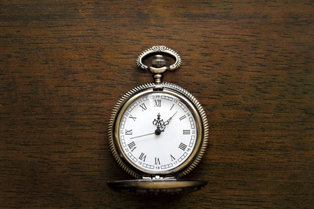 Antique pocket watch on a wood board