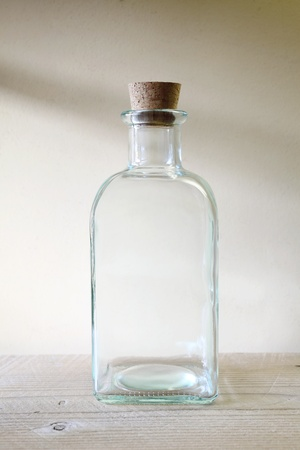 Oude glazen fles op wonnden plank