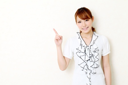 Portrait of young japanese business woman pointing