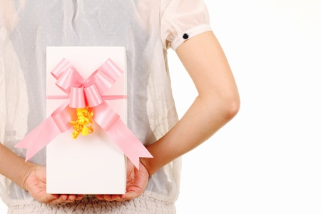 Young woman hide behind back the white gift box photo
