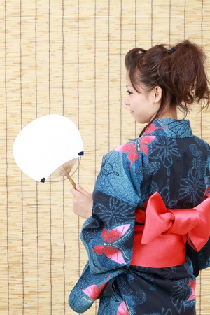 Japanese woman in traditional clothes of Kimono with japanese fan  photo
