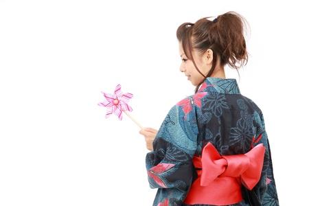 風車と着物の伝統的な服で日本人女性