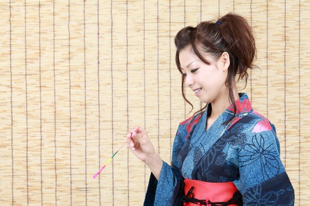 Japanese woman in traditional clothes of Kimono, with sparkler photo