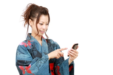 Young japanese woman in clothes of kimono with smartphone photo