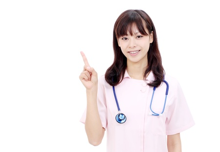 Happy young japanese female nurse pointing Imagens