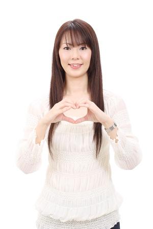 그녀의 손가락으로 마음을 보여주는 젊은 아시아 여자