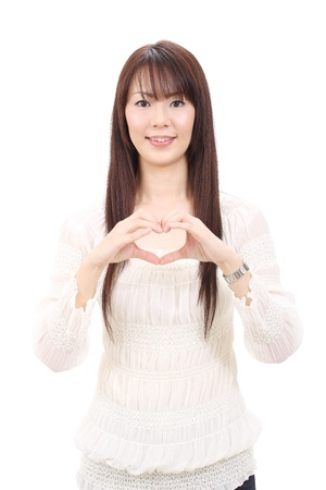 Young asian woman showing a heart with her fingers photo