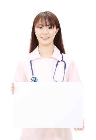 Young asian female nurse holding a blank white board photo