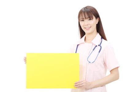Young asian female nurse holding a blank board photo