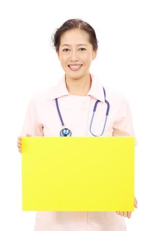 Asian female nurse holding a blank white board photo