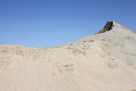 Grey sand mound and clear blue sky photo