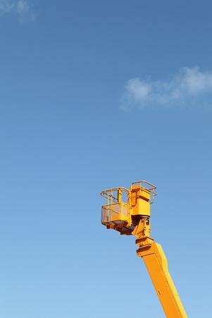 Cherry picker platform against a blue sky photo