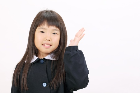 Little asian schoolgirl rise hand showing blank sign photo