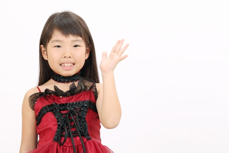 Lovely little asian girl rise hand showing blank sign photo