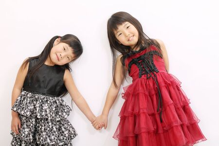 girls holding hands: Two asian girls holding hands and smiling