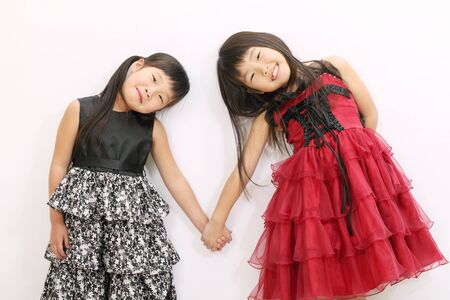 decent: Two asian girls holding hands and smiling
