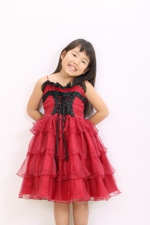 Little asian girl wearing dress, with hands at her back photo