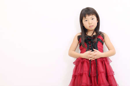 Little asian girl wearing dress, with hands crossed photo