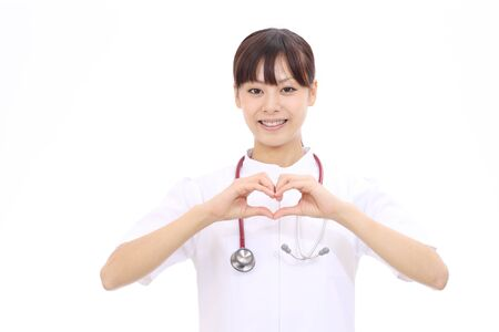 Young asian female nurse shows fingers heart photo