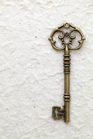 Antique key on handmade rice paper Stock Photo