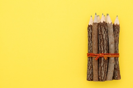 Wooden pencil on yellow paper background   photo